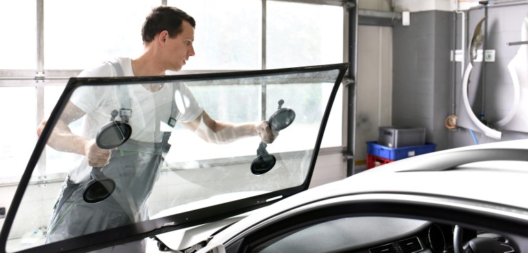 Young mechanic in car workshop changing the windscreen of a car